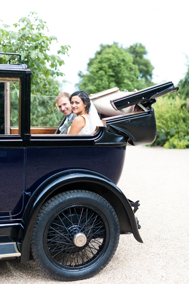 vintage black car with bride and groom