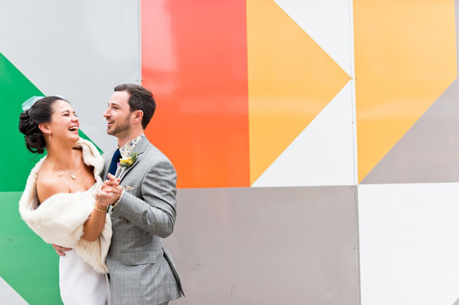 Fun wedding day portrait of bride and groom using colourful background
