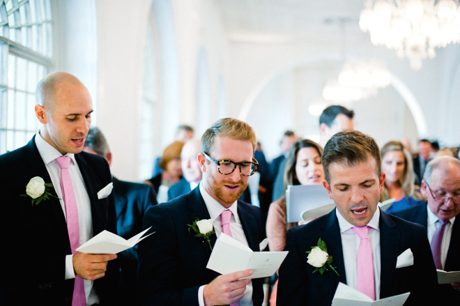 ushers in pink ties singing hymns at central london wedding